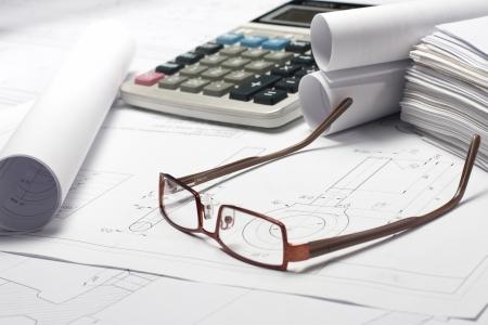glasses laying on opened blueprint