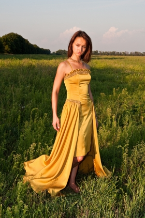Stock Photo  Girl dressed in yellow dress at the field Stock Photo