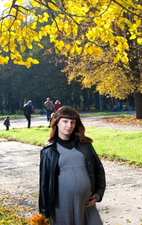 Pleasured pregnant woman in autumn park  photo