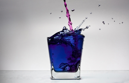 Water splash in a glass with colour water on white backgroung. Pink and blue. Stock Photo - 13721104