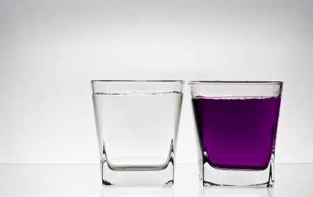 cocaine: Two glases with water, pink water in ine of it. Isolated on white background.
