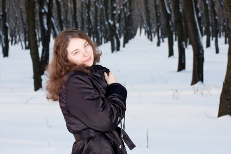 Beautiful, happy young adult female in winter forest. Looking at the camera.