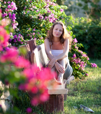 Woman sitting on the bench inside the flowers garden Stock Photo