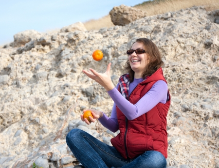 Woman having fun by catching orange photo
