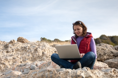 Woman working on the laptop, sitting at the sea coast Stock Photo - 17544092