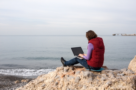Woman working on the laptop, sitting at the sea coast Stock Photo - 17544091