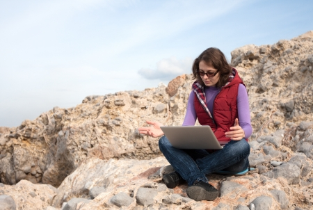 Young woman working on a rock on laptop Stock Photo - 17544081