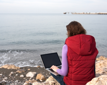Woman working on the laptop, sitting at the sea coast