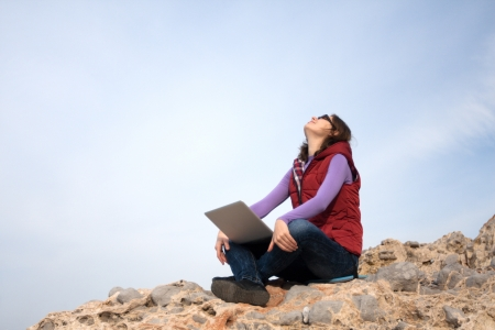 Young woman working on a rock with her laptop Stock Photo
