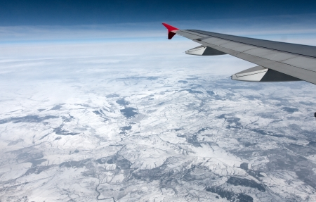 View of airplane wing abowe the clouds and land Stock Photo