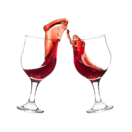 Two wine glasses clinking together in a splashy toast at the white backgroung