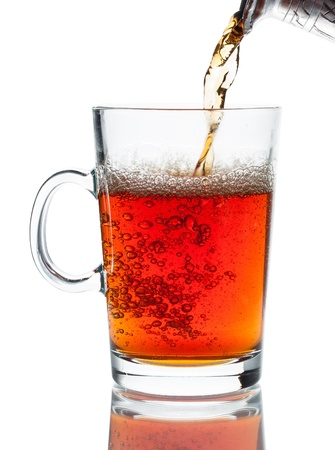 Pouring a cup of hot black tea isolated on white Stock Photo