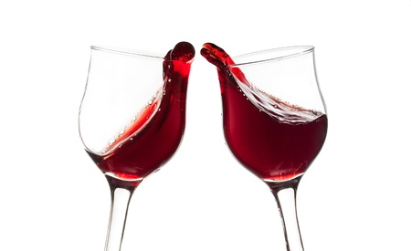 Two red wine glasses in toast gesture isolated Stock Photo