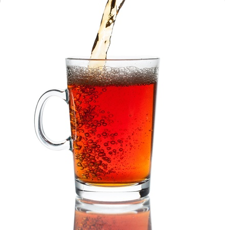 Cup of tea pouring with splash on white background
