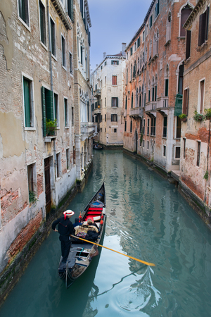 Venetian gondolier punting gondola through green canal waters of Venice Italy 写真素材