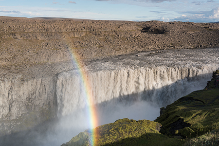 The most powerful waterfall in Europe - majestic Dettifoss in Iceland with a beautiful rainbow Imagens