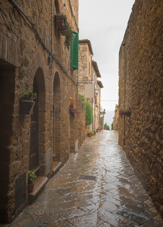 Flowery streets on a rainy spring day in a small magical village Pienza, Tuscany