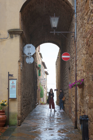 PienzaItaly - 050518: Two women hiding from the rain under old arch in Pienza, one of the most beautiful old towns in Toscana, Italy Editorial
