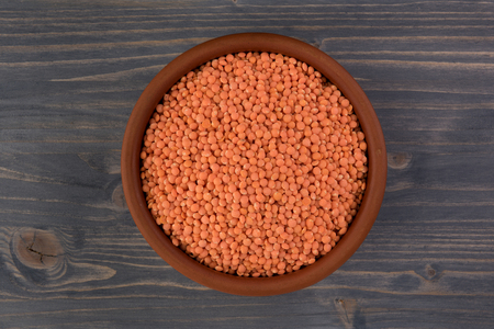 Red lentils in clay plate on wooden table background