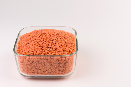 Red lentils in glass plate isolated on white background