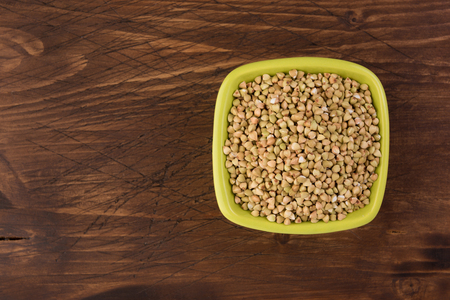 Natural fresh green buckwheat in ceramic bowl on wooden background. Top view 스톡 콘텐츠