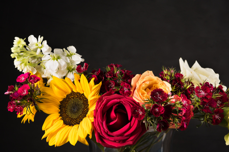 Bouquet of white yellow and red flowers in a vase on a dark background