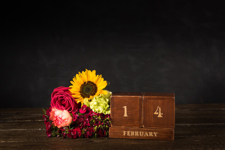 Happy Valentine's Day vintage wooden Perpetual calendar for February 14 on a black background and a bunch of various flowers