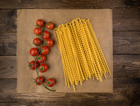 Pasta and tomatoes on dark wooden background with copy space. Top view. Vegetarian food, health or cooking concept