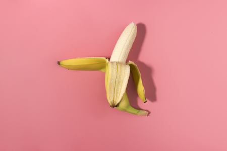Fresh peeled banana on pink background with contrast shadows, flat lay