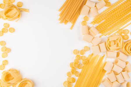 Food and drink concept - various uncooked pasta on white background. Top view