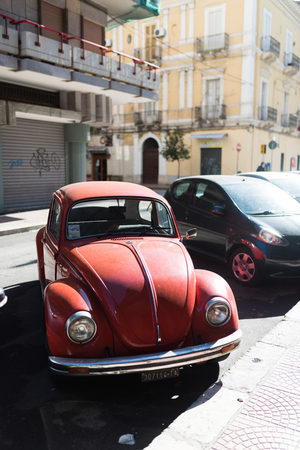 Taranto, Italy - February 3, 2019: Red retro car Volkswagen Beetle parked at the city street, narrow depth of field Фото со стока