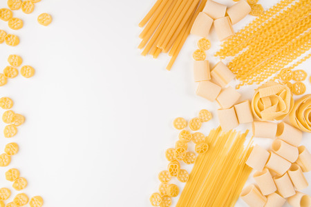 An overhead photo of different types of pasta, including spaghetti, penne, fusilli, and others, flay lay on a white background with a place for text