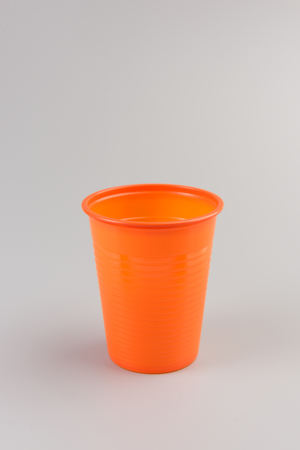 Round orange Plastic Cup isolated on grey background