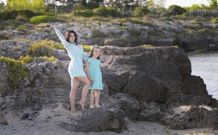 Happy loving family mother and daughter having fun on the beach at sunset - Mum playing with her kid next see in holidays - Parent, vacation, family lifestyle concept Imagens