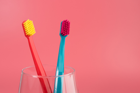 Cup with toothbrushes on table against color background. Dental care Фото со стока