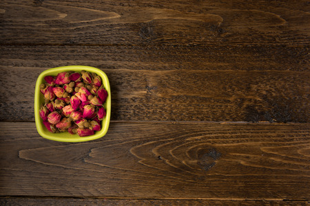 tea rose buds in a clay drinking bowl  isolated on wooden background, top view