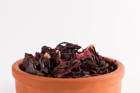 petals of dry hibiscus tea  in the clay pot isolated on white background