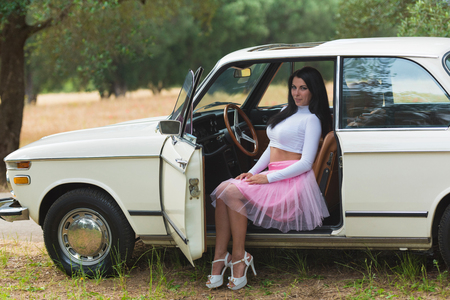 Summer car on street with forest landscape. Slim young woman in pink dress.