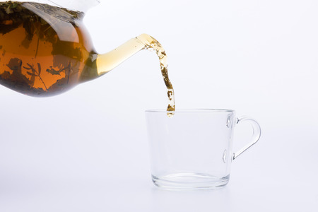 tea pouring in the cup isolated on white