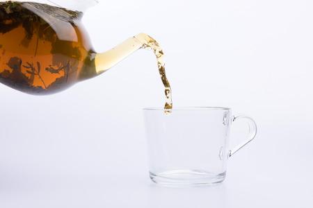 Tee gießt in die Tasse isoliert auf weiß
