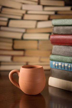 clay cup and many books on a wooden table