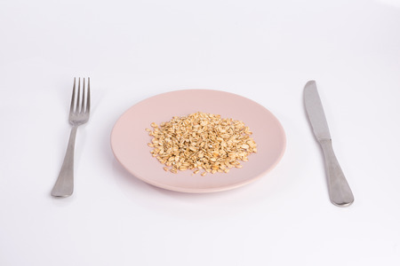 pile of oatmeal on a plate isolated on white background Stock Photo