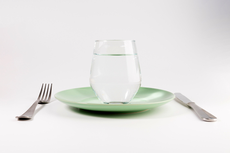 glass of water in a plate with knife and fork isolated on white background