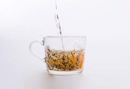 Water pouring into glass cup with tea and slices of orange isolated on white