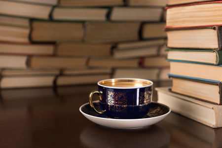 cup of tea and many books on the desktop