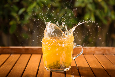 Splash in the transparent cup of fresh beverage outdoors, summertime Reklamní fotografie