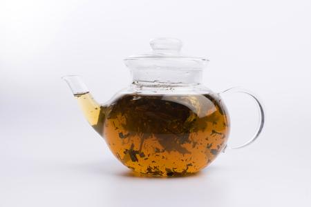 Teapot with green bilolgical tea isolated on white background 版權商用圖片