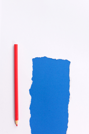 White torn paper over blue background with pencil