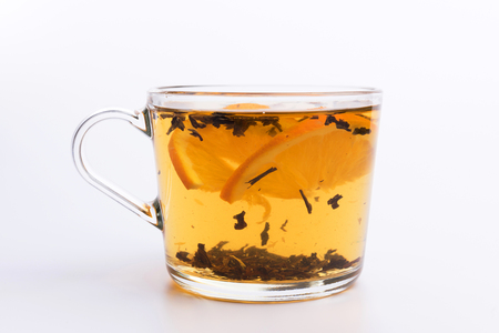 Tasse en verre de thé aromatique chaud sur fond blanc