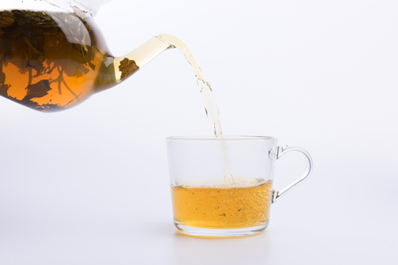 Tea pouring into glass cup isolated on white Stock Photo